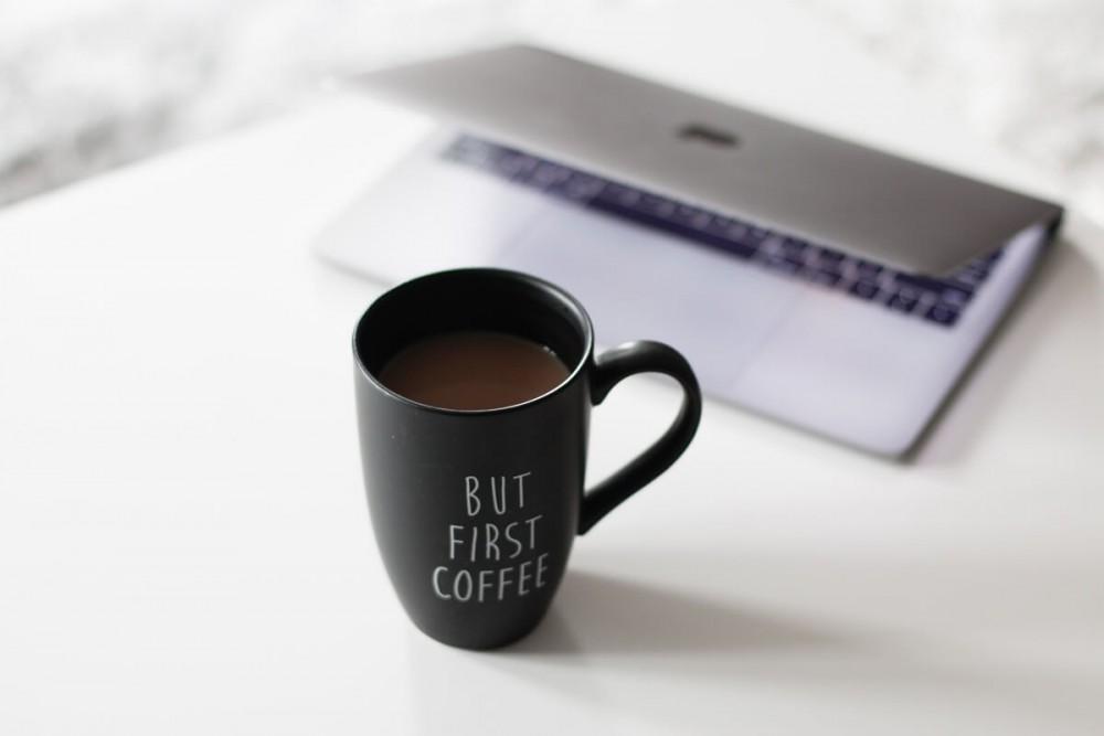 Kubek z kawą na stoliku z laptopem