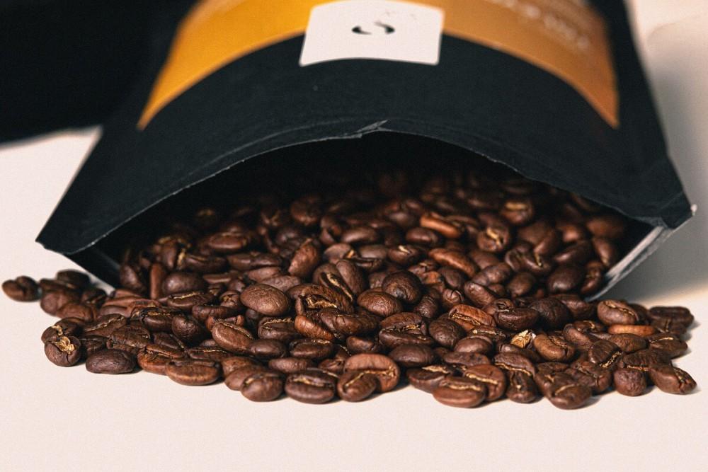 Kawowe ziarna wysypujące się z opakowania